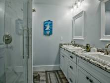 Continuing the clean, crisp theme into the master bathroom complete with double vanities & a walk-in shower