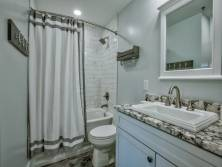 Elegantly furnished guest bathroom is complete with a shower/tub combo